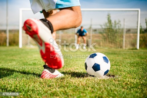 Soccer player kick the ball at the penalty