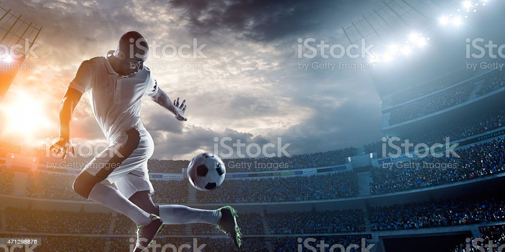 A soccer player kicking a ball in the stadium stock photo