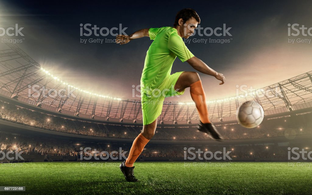 Soccer player kicking a soccer ball on a playing field stock photo