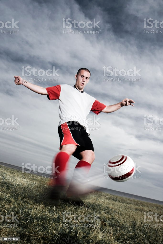 Soccer Player Kicking Ball Against Stormy Sky royalty-free stock photo