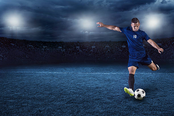 Soccer player kicking ball in a large stadium at night stock photo