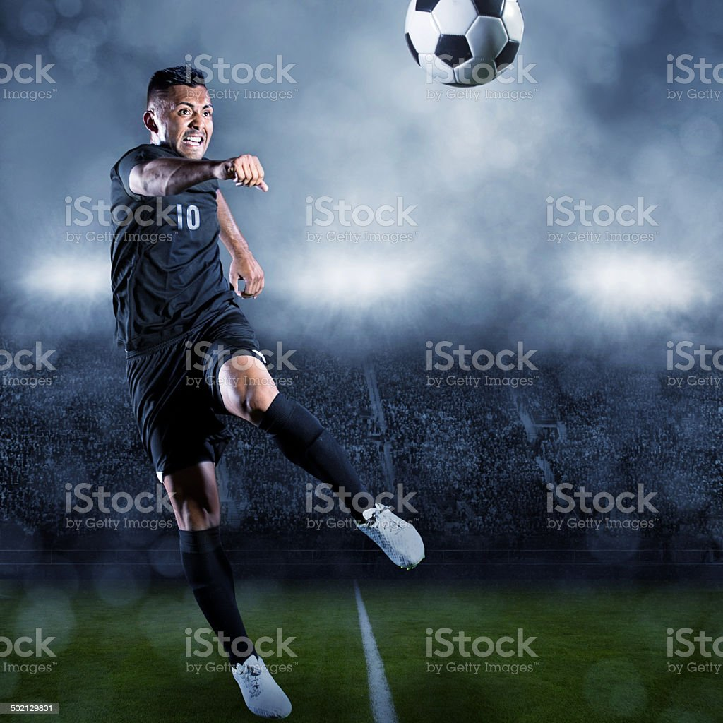 Soccer player kicking ball in a large stadium stock photo