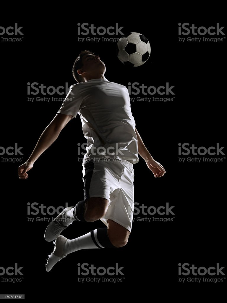 Soccer player kicking ball in a stadium on black background stock photo