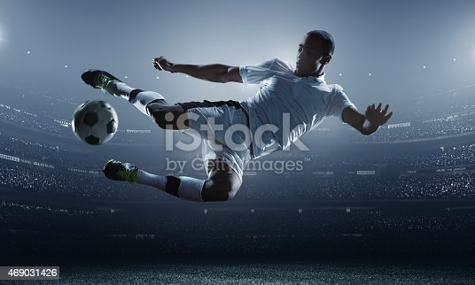 A male soccer player makes a dramatic play by jumping horizontally. He attempts to kick the ball with his feet. The stadium is dark behind him. Only the lights of the stadium shine brightly, creating a halo effect around the bulbs.