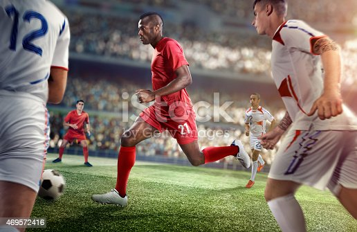 A male soccer player makes a dramatic play. He attempts to kick the ball with his feet. The stadium is blurred behind him. The opposite team players are going to block the ball. All players are wearing generic unbranded basketball uniform. The stadium is 3D rendered.