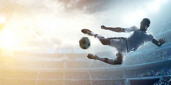A male soccer player makes a dramatic play by jumping horizontally. He attempts to kick the ball with his feet. The stadium is blurred behind him. Only the lights of the stadium shine brightly, creating a halo effect around the bulbs.