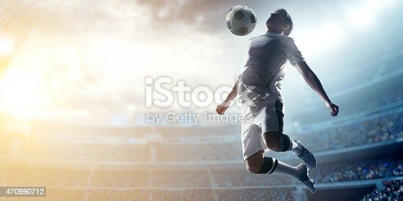 istock Soccer player kicking ball in stadium 470990712