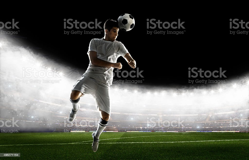 A male soccer player makes a dramatic play by jumping vertically. He...