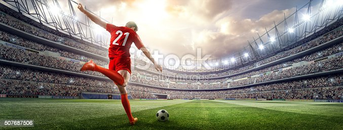 istock Soccer player kicking ball in stadium 507687506