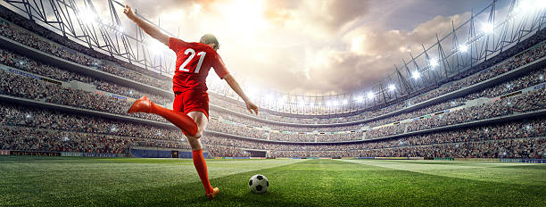 soccer player kicking ball in stadium - soccer stock photos and pictures