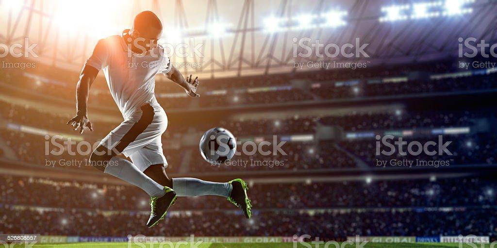 Soccer Player Kicking Ball on stadium stock photo