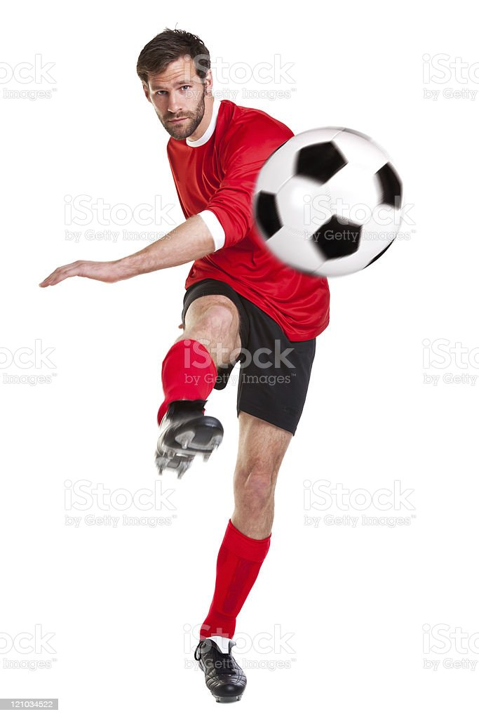 Soccer player kicking ball on white background stock photo
