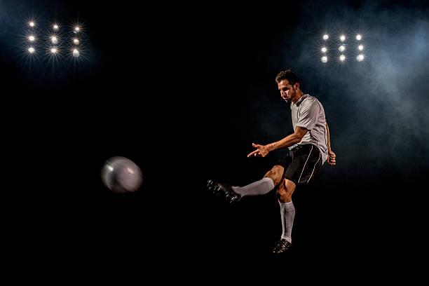 Soccer player kicking stock photo
