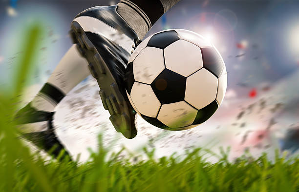 soccer player kicking soccer ball in motion stock photo