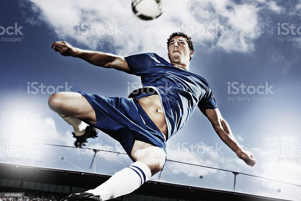 Soccer player kicking soccer ball stock photo