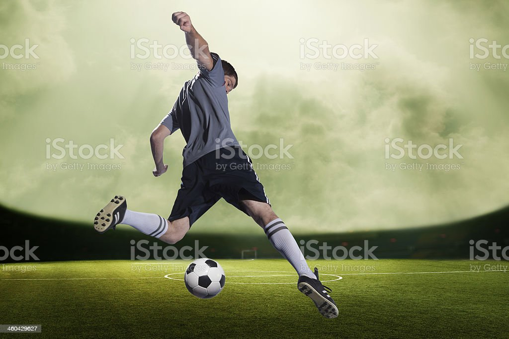 Soccer player kicking the ball in a stadium stock photo