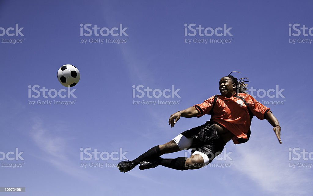 Soccer Player Kicking the ball in sky stock photo