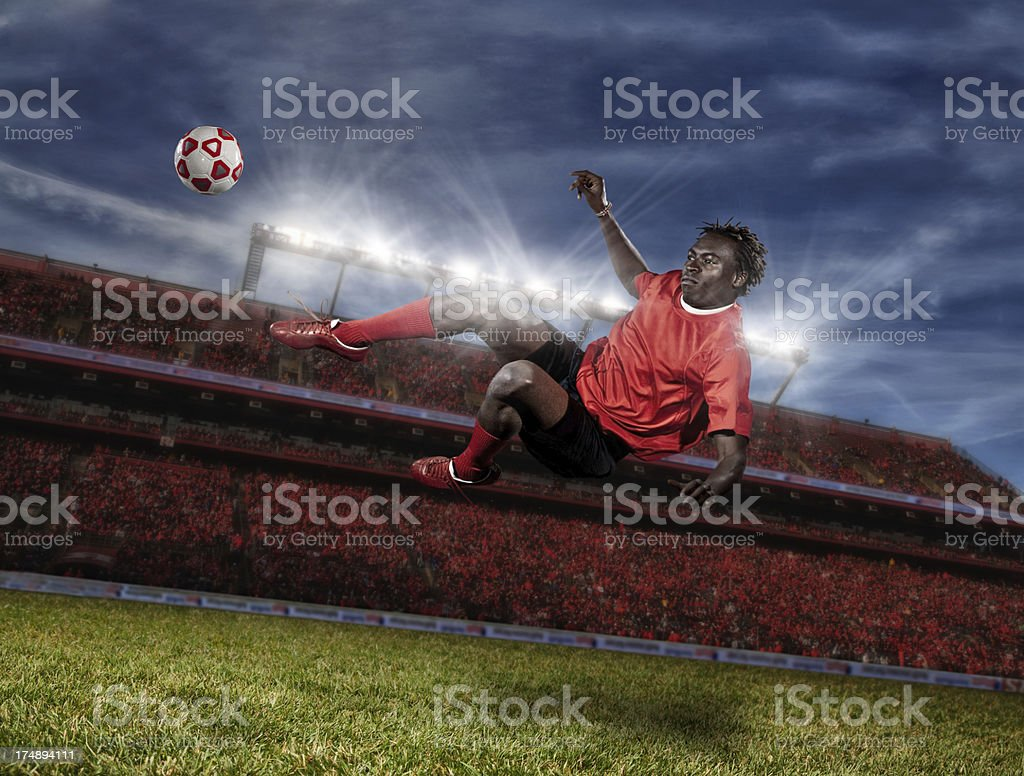 Soccer player kicking the ball while jumping in mid-air stock photo