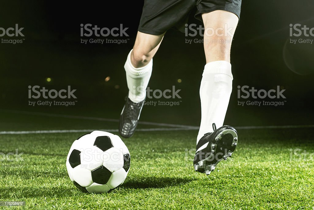 Soccer player kicks ball with full power royalty-free stock photo