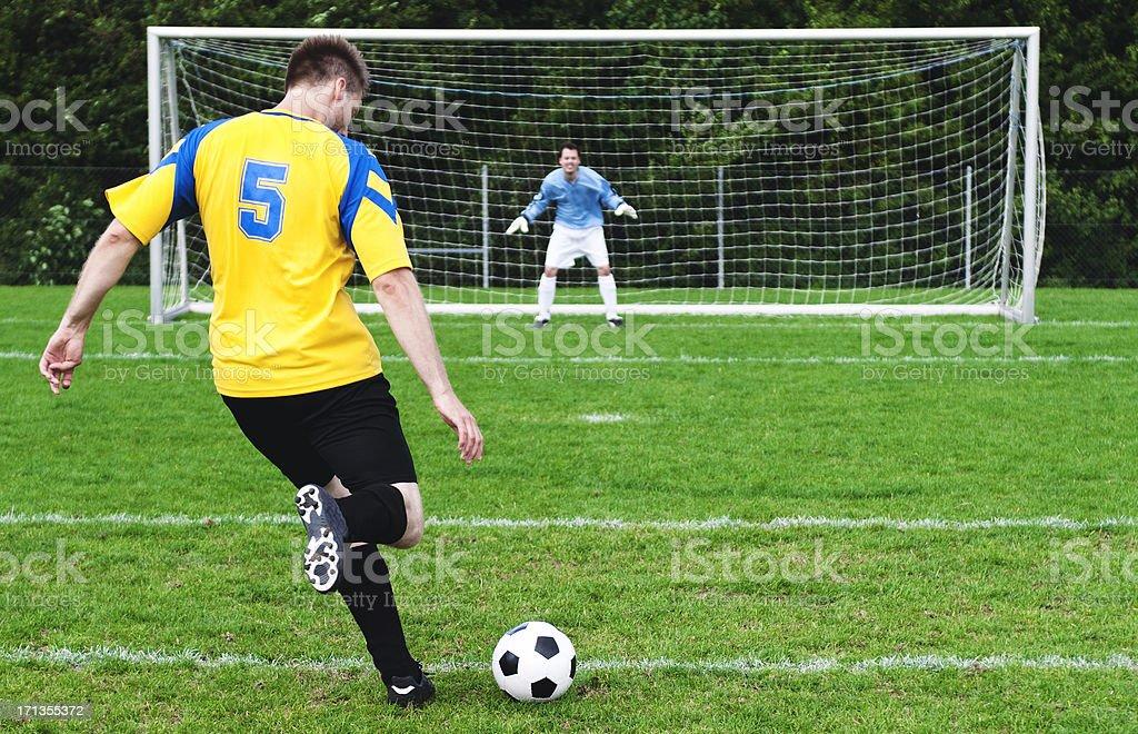 Soccer player kicks football - goalkeeper ready royalty-free stock photo