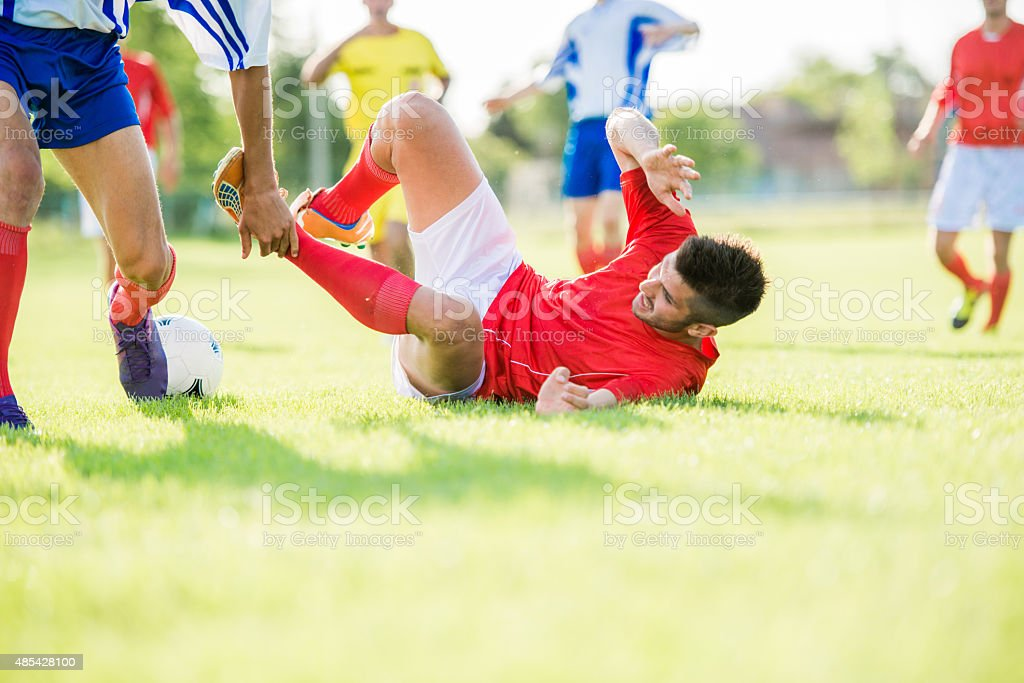 Soccer player lying on grass after foul during a match. stock photo