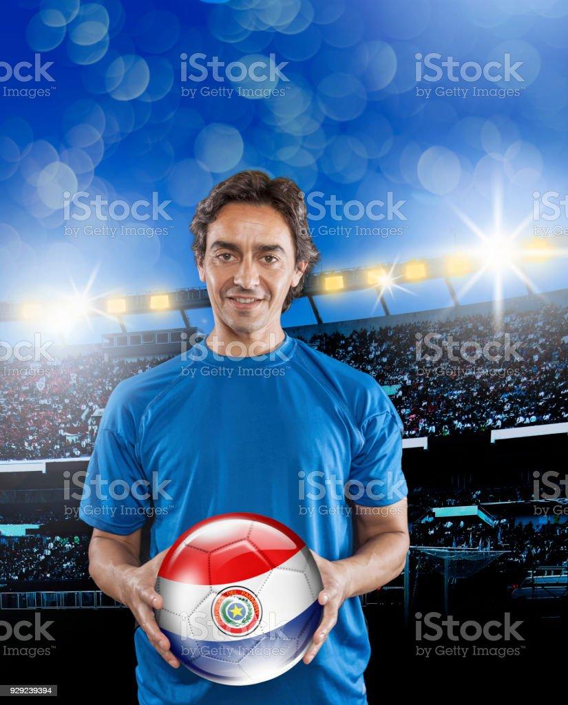 Balón de retención de Paraguay fútbol jugador con bandera paraguaya en el estadio - foto de stock
