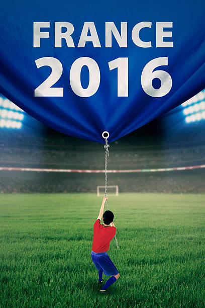 fußball spieler leitet banner im stadion - fußball poster stock-fotos und bilder
