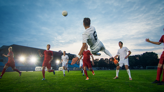 Soccer Player Receives Successful Pass and Kicks Ball to Score Amazing Goal doing Bicycle Kick. Shot Made on a Stadium Championship.
