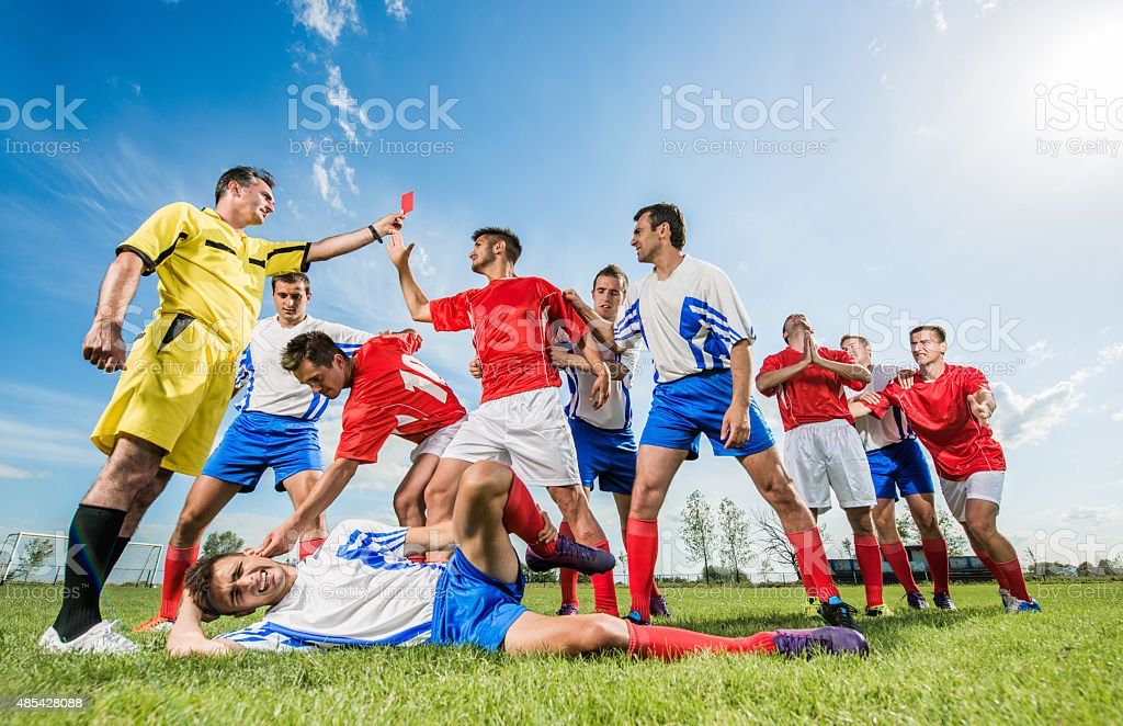 Soccer player receiving a red card for making a foul. stock photo