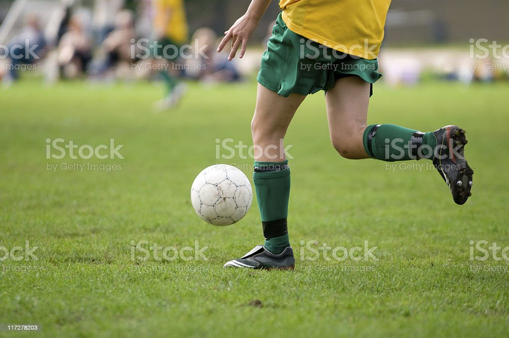 Soccer player runs while kicking the ball royalty-free stock photo