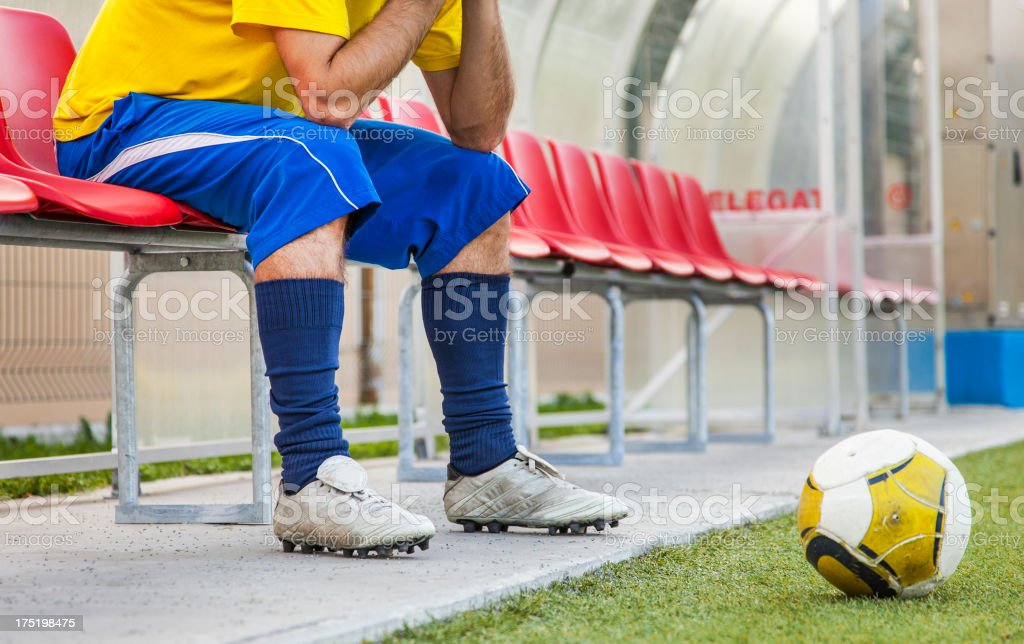 Soccer player sitting on a red bench with a soccer ball royalty-free stock photo