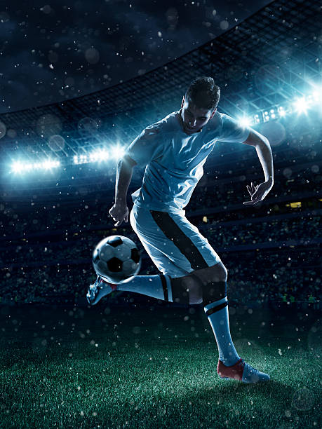 Soccer player tackling a ball on stadium stock photo