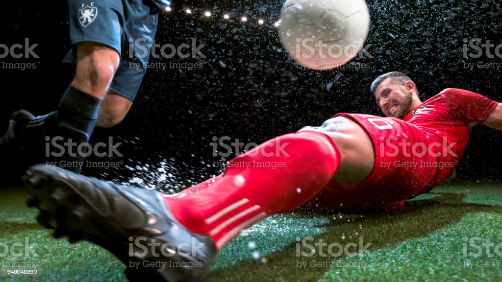 Soccer player trying to slide tackle his opponent stock photo