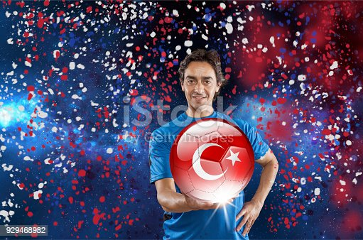istock Soccer player Turkey holding ball with turkish flag under confetti 929468982