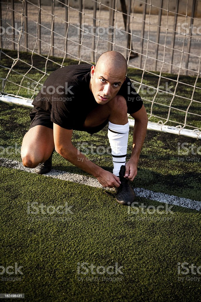 Soccer Player Tying His Shoe at the Goal royalty-free stock photo