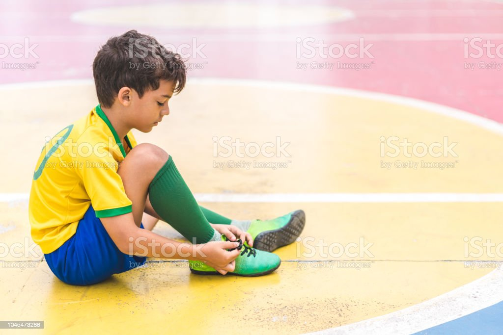 Soccer player tying laces him boots on court. stock photo