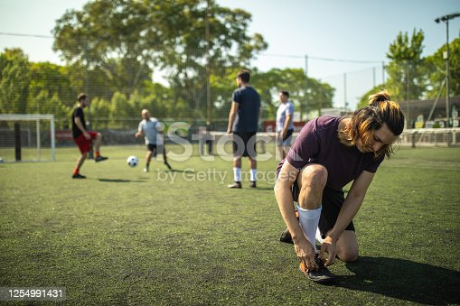 Men with long hair sitting and tying shoelace on soccer shoe at soccer court while other teammates doing warm-up routine behind him during sunny day at Buenos Aires