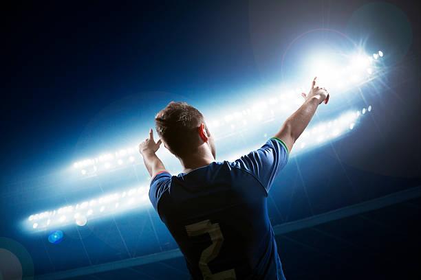 Fußballspieler mit Arme heben jubeln, Stadion bei Nacht – Foto
