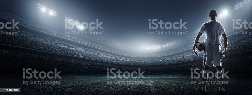Soccer player with ball in stadium stock photo