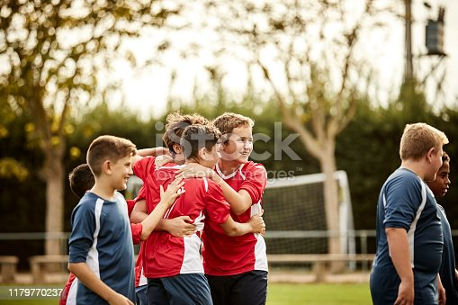 Happy soccer players are huddling on ground. Boys are celebrating success after match. They are on sports field.