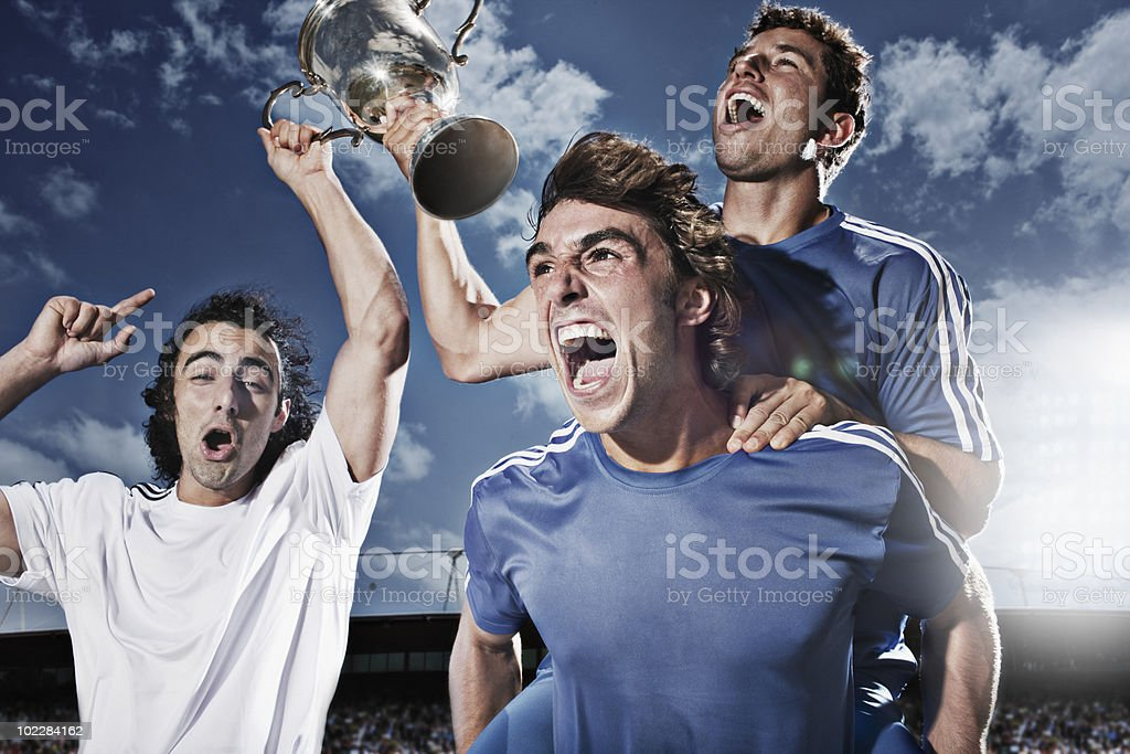 Soccer players cheering with trophy stock photo