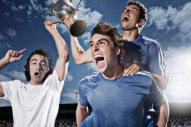 soccer players cheering with trophy - sports championship stock photos and pictures