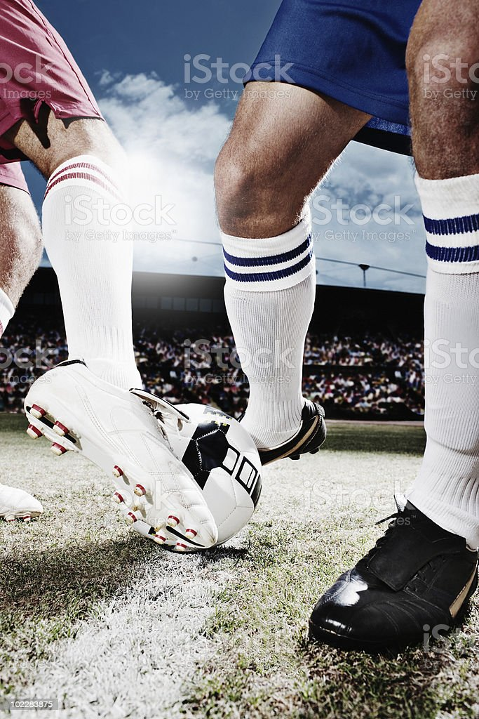Soccer players competing for soccer ball stock photo