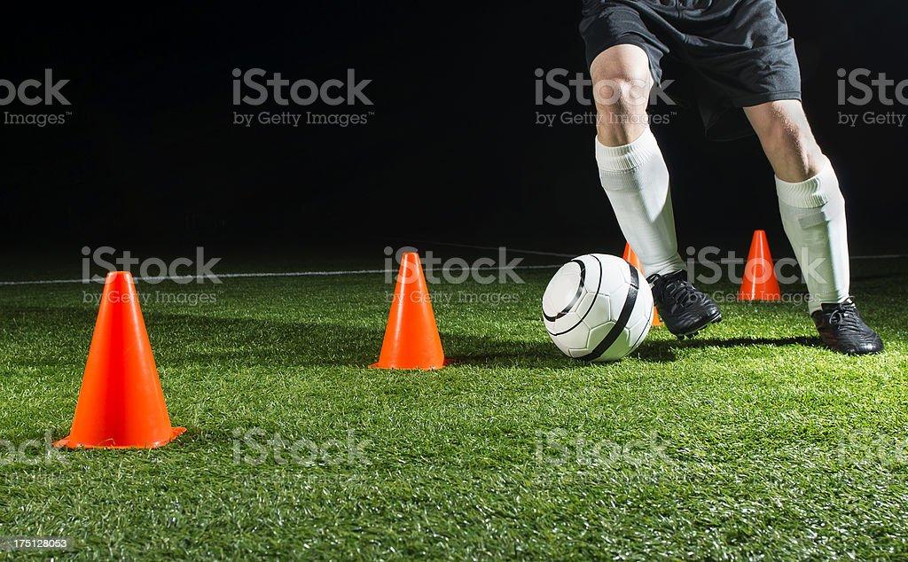 A soccer players feet kicking a ball through cones stock photo