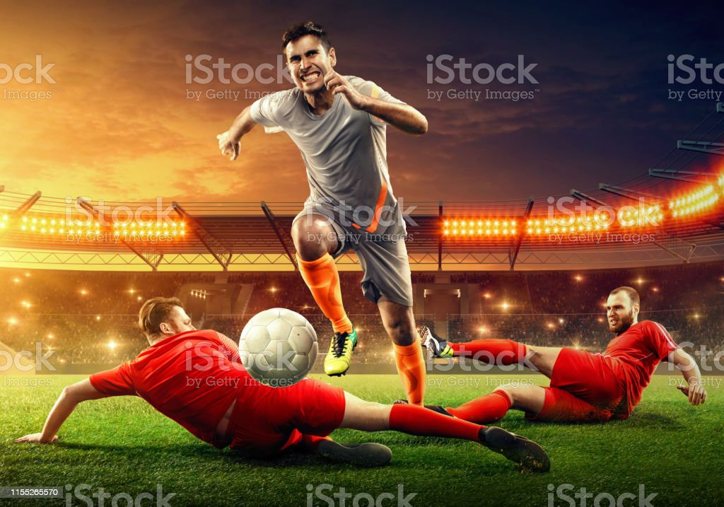 Three professional soccer players on a soccer field fight for a ball....