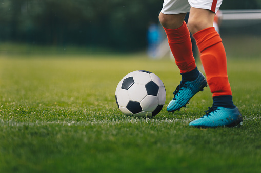 Soccer Players Legs. Footballer Kicking Ball on Natural Grass Field. Closeup Image of Soccer Boy in Cleats and Soccer Socks Running Ball
