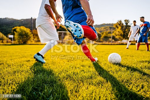 Soccer players playing football at sunset.