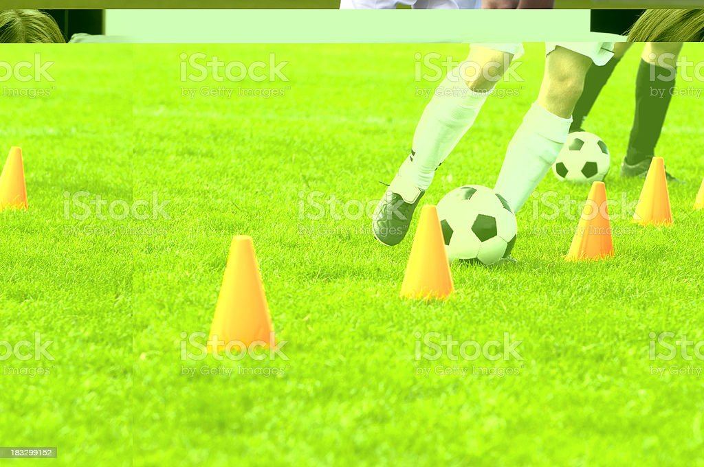 Soccer players run with football past cones during training session stock photo