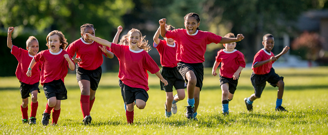 A multi-ethnic group of elementary age children running across the field cheering victoriously over their winning game.