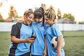 Smiling soccer girl showing mobile phone to friends. Female sports team is standing on field. They are wearing blue jerseys.